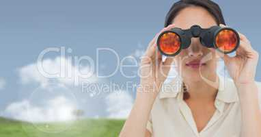 Businesswoman in nature field with binoculars