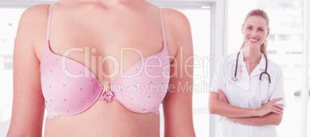 Composite image of mid section of woman wearing pink bra for breast cancer social issue