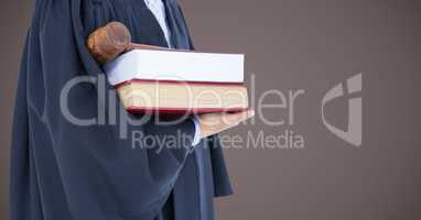 Judge mid section with books and gavel against brown background