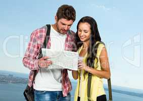 Millennial couple with map against blurry sky and coastline