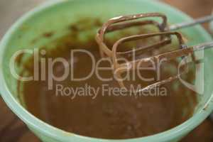 Close up of electric mixer by bowl with chocolate batter