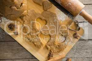 Pastry dough and pastry cutter on cutting board by rolling pin