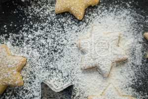 Close up of flour over star shape cookies
