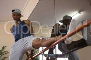 Male dancer stretching leg by mirror on barre