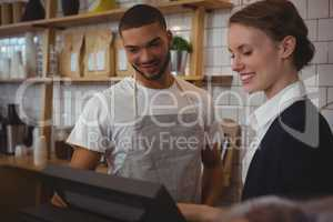 Owner with waiter looking into cash register in cafe