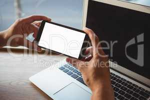 Cropped hand of man holding phone over laptop