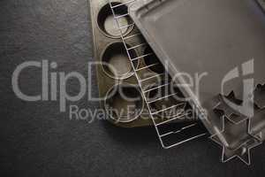 Overhead view of various pastry cutter and baking sheet with cooling rack on muffin tin