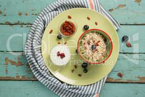Plate of breakfast cereal with fruits and yoghurt on wooden table