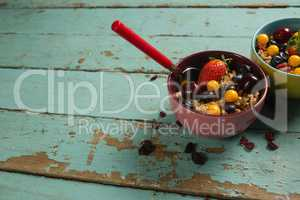 Bowls of breakfast cereals and fruits with spoon