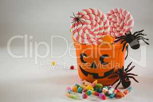 Bucket with candies and decoration over white background