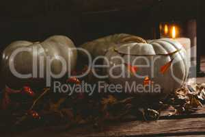 White jack o lanterns with autumn leaves on table