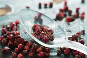 Pink peppercorn and spoon on wooden table