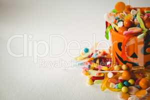 Orange bucket with various sweet food during Halloween on white background