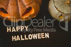 Happy Halloween text by jack o lanterns over black background