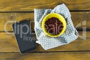 Pink peppercorn in bowl and mobile phone
