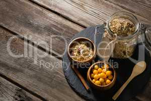 Bowl of cape gooseberry and jar of muesli on table