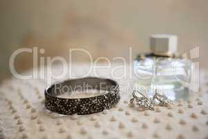 Close up of earring with bangle and perfume bottle
