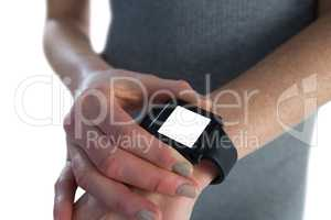 Mid section of businesswoman adjusting smart watch