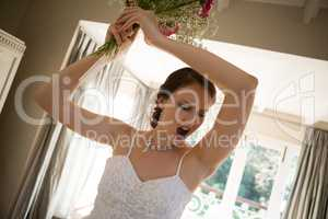 Tilt image of angry bride throwing bouquet at home