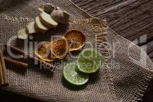 Sliced ginger, dried orange and lemon with cinnamon stick on textile