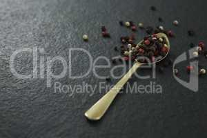 Black pepper and white pepper seeds in a spoon