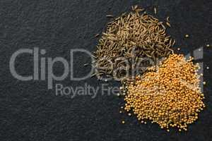 Cumin seeds and spice on black background