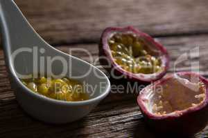 Two passion fruit and spoon with passion fruit pulp on wooden table