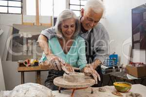 Senior man assisting senior woman in making pottery during drawing class