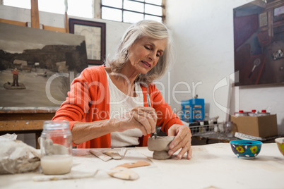 Attentive senior woman shaping a clay pot