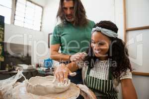 Man assisting woman in pottery