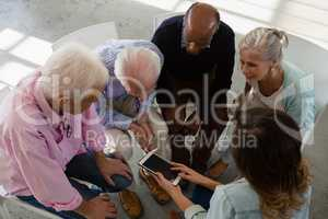 High angle view of teacher showing tablet while sitting with senior adults