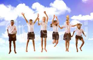 Composite image of full length of students in school uniforms jumping