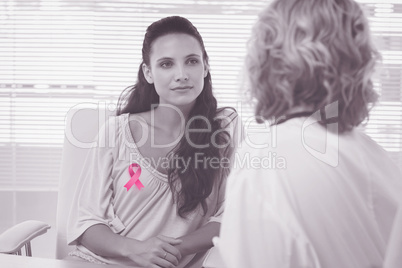 Composite image of female patient listening to doctor with concentration in medical office