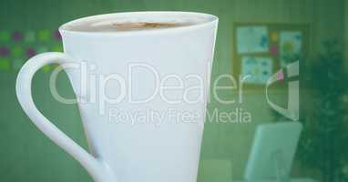 White coffee cup against blurry office with green overlay