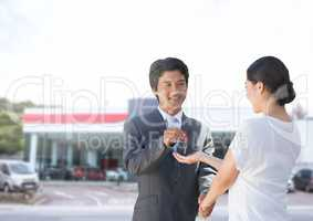 Businessman handing car keys to woman at car auto store