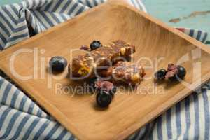 Granola bar and blueberry on wooden plate