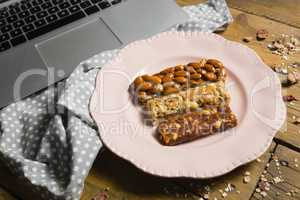 Dry fruit bars and laptop on wooden table