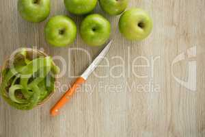 Overhead view of granny smith apples by peel in basket