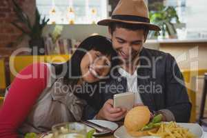 Man with young woman using phone at cafe