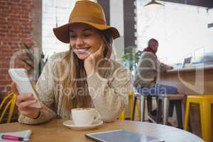 Smiling woman using phone in cafe
