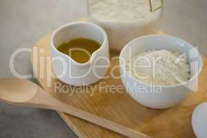 Flour and oil in containers on cutting board