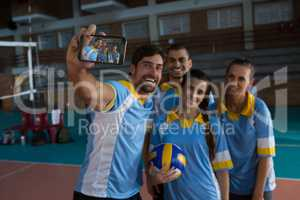 Smiling male volleyball player with team taking selfie