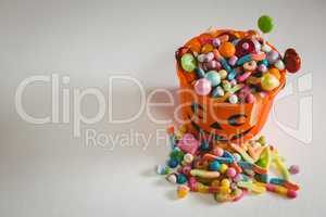 Bucket with various sweet food on white background during Halloween