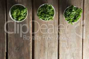 Overhead view of kale arranged side by side in bowls on table