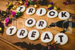 Cookies with trick or treat text by decorations and chocolates on table