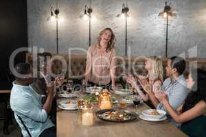 Group of happy friends applauding woman while dining