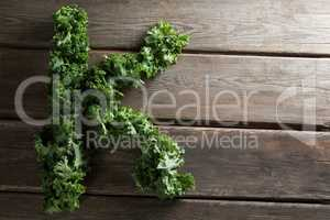 Letter K made with kale leaves on wooden table