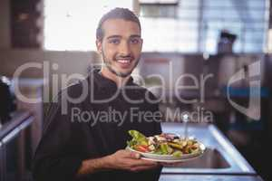 Portrait of smiling young waiter holding salad plate at commercial kitchen