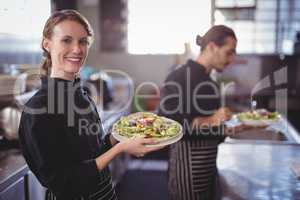 Portrait of smiling young waitress holding fresh salad against waiter at commercial kitchen