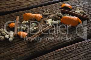 Cinnamon sticks, orange peel and dried ginger on a wooden table